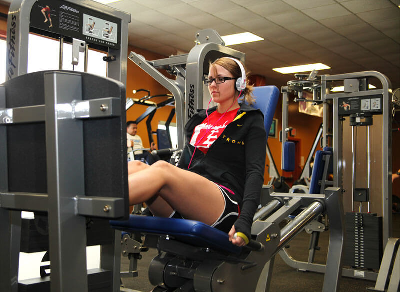 woman exercises on leg press machine