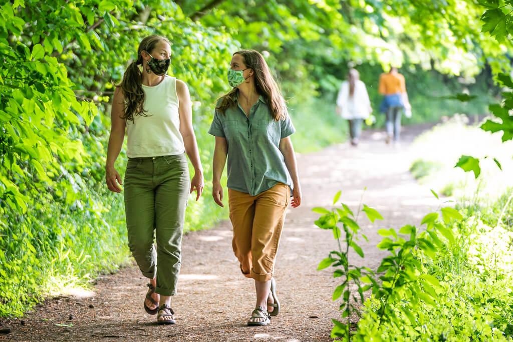 two women walking in a park wearing masks
